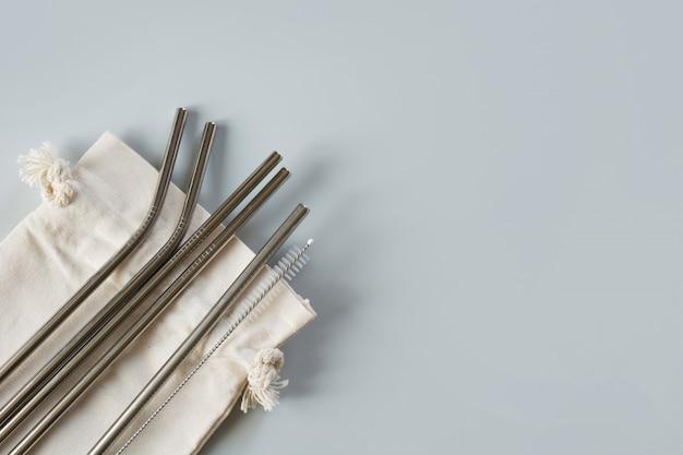 Metallische strohhalme mit baumwollbeutel auf grau.