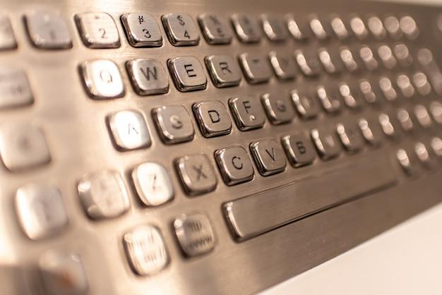 Metallische tastatur mit buchstaben und zahlen, zum von informationen in einen kassierer einzugeben.
