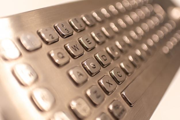 Metallische tastatur mit buchstaben und zahlen zur eingabe von informationen in einen kassierer.