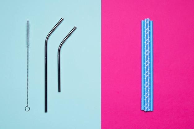 Metallische und papierstrohe der draufsicht auf zweifarbigem hintergrund