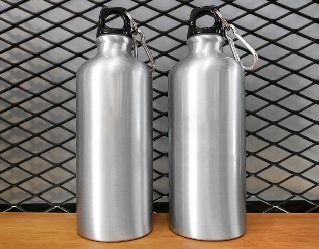 Metallische wasserflasche und -karabiner auf hölzernem regalhintergrund.