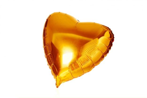 Metallischer ballon des goldgroßen herzens lokalisiert auf weiß