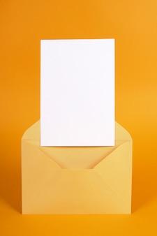 Metallischer goldumschlag mit leerer mitteilungskarte oder -einladung