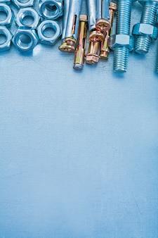 Metallischer hintergrund mit konstruktionskonzept aus rostfreiem ankerbolzen, schrauben und muttern