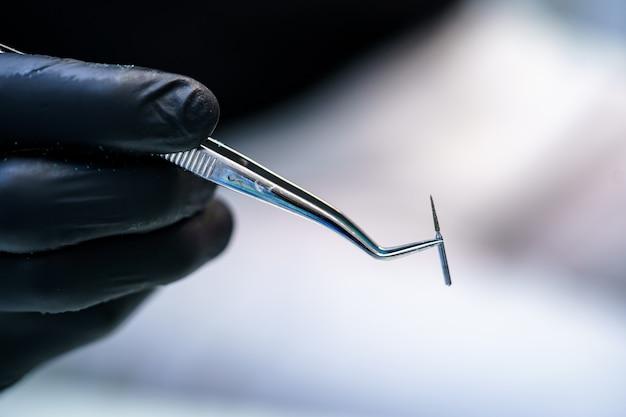 Metallischer kopf für zahnarztbohrer. zahnarzt hält instrumente in den händen.
