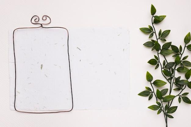 Metallischer rahmen auf strukturiertem papier mit grünen künstlichen blättern auf weißem hintergrund