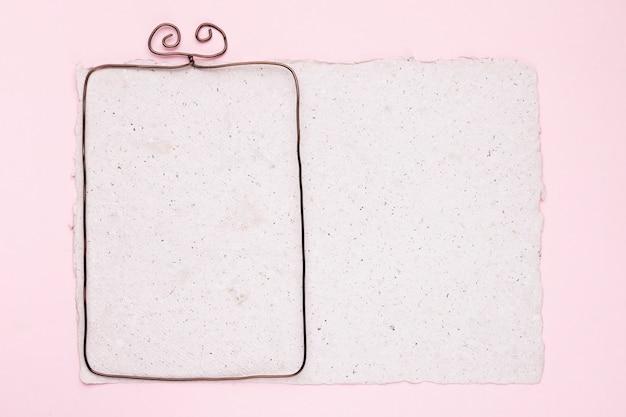 Metallischer rahmen auf weißem beschaffenheitspapier über dem rosa hintergrund