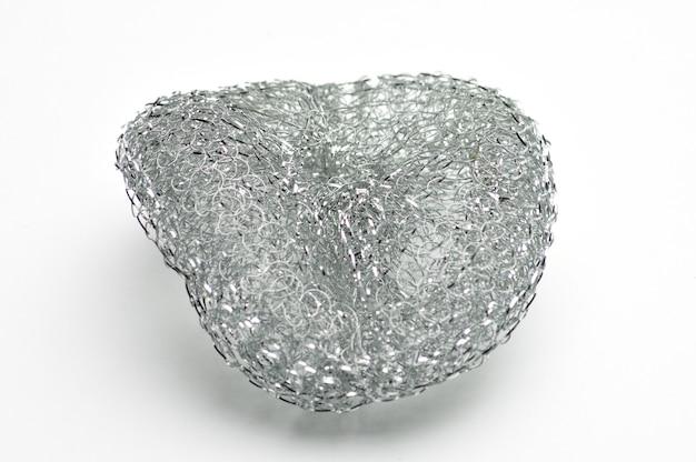 Metallischer schwamm zum geschirr spülen und zum installieren auf isolierter weißer oberfläche