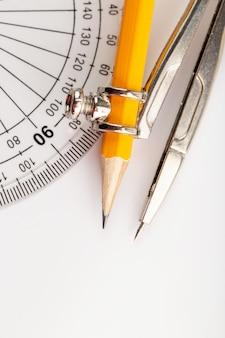Metallischer zeichnungskompass lokalisiert mit bleistift auf weißer wand