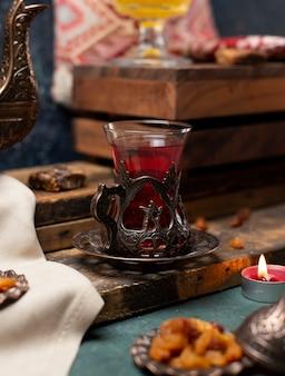 Metallisches dekoratives glas schwarzer tee auf dem hölzernen brett