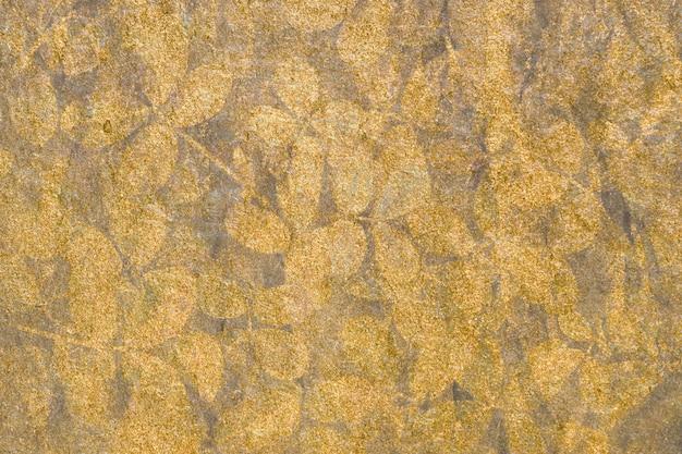 Metallisches gold verlässt gemusterten hintergrund