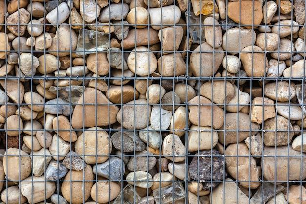 Metallisches korbnetz gefüllt mit natursteinen als zaun