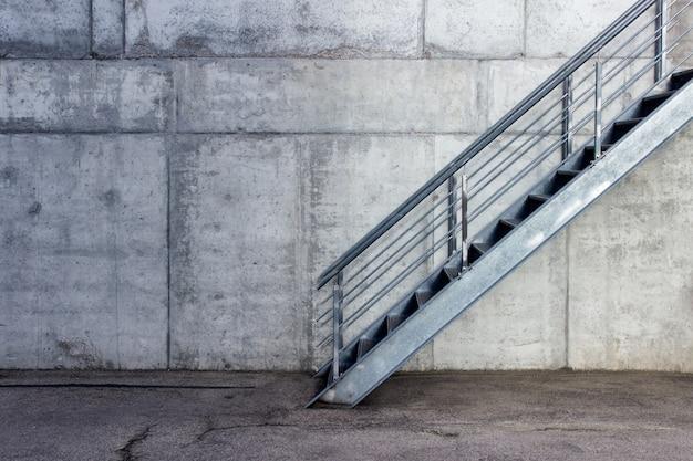 Metallisches treppenhaus auf dem hintergrund der grauen zementwand