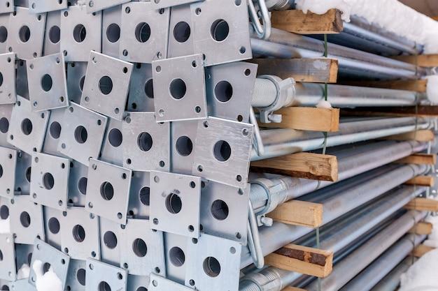 Metallkonstruktionen in einem lagerhaus in stapeln. metallstützen für gerüste und schalungen. weichzeichner und bokeh.outdoor lagerung von baumaterialien und metallkonstruktionen.