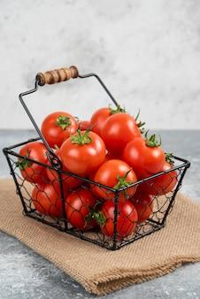 Metallkorb mit frischen bio-tomaten auf marmor.