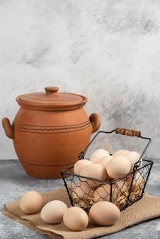 Metallkorb mit rohen hühnereiern und antiker vase auf marmoroberfläche.