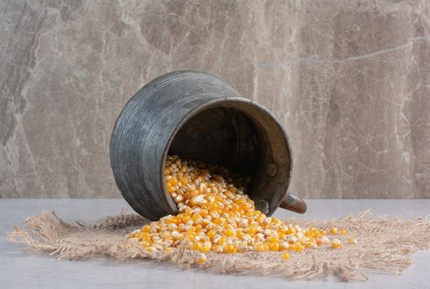 Metallkrug, der maiskörner auf ein stück stoff auf marmor ausgießt.