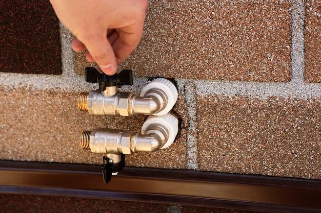 Metallkugelhähne für wasser sind außerhalb der hausgewindeanschlüsse installiert, die die ventile öffnen und schließen