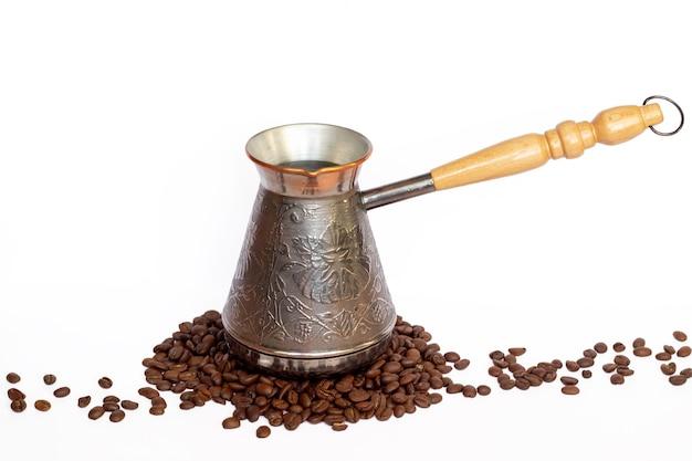 Metallkupferbrauner kaffeetürke mit holzgriff ist auf den kaffeebohnen lokalisiert auf weißem hintergrund. kaffeekanne, kaffeemaschine