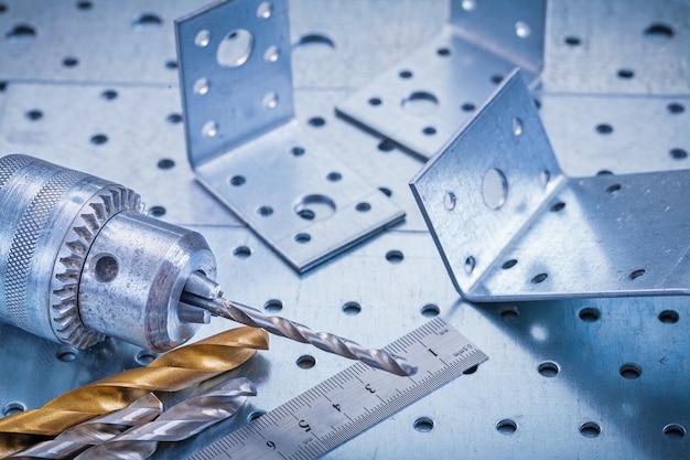Metalllinealbohrer und winkelstangen auf perforiertem metallischem hintergrundkonstruktionskonzept