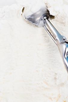 Metalllöffel im selbst gemachten eiscremehintergrund der vanille