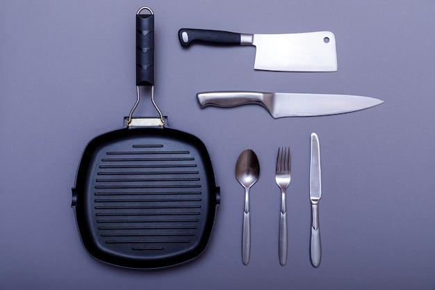 Metallmesser mit schwarz auf grauem tisch, grillpfanne, handtuch. flache lage, layout.