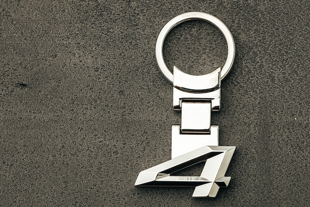 Metallnummer vier autoschlüssel auf dunklem betonhintergrund schließen