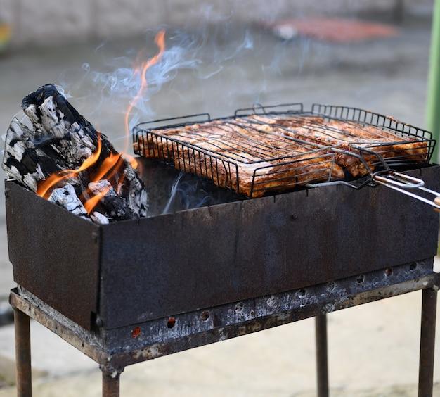 Metallpfanne mit brennendem holz und fleisch auf dem grill, grill