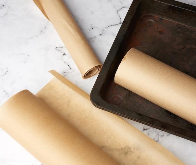 Metallpfanne und rollen des braunen pergamentpapiers auf einem weißen tisch
