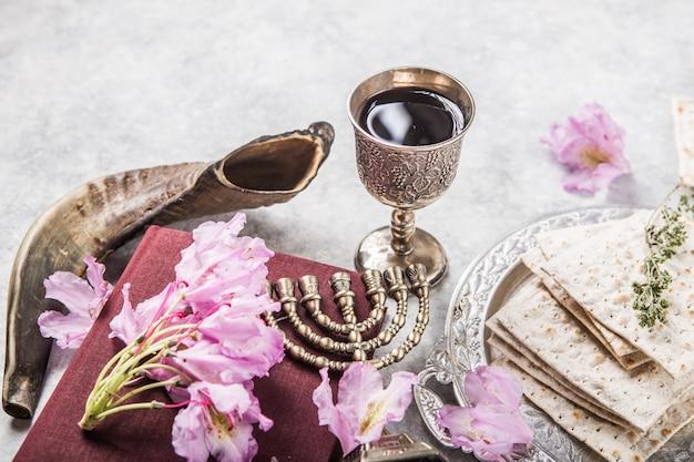 Metallplatte mit matzah kiddush cup, shofar horn auf hellem hintergrund präsentiert als pessach seder fest oder mahlzeit mit kopierraum. jüdische traditionelle gegenstände, yarmulke, tallit, gebetbuch