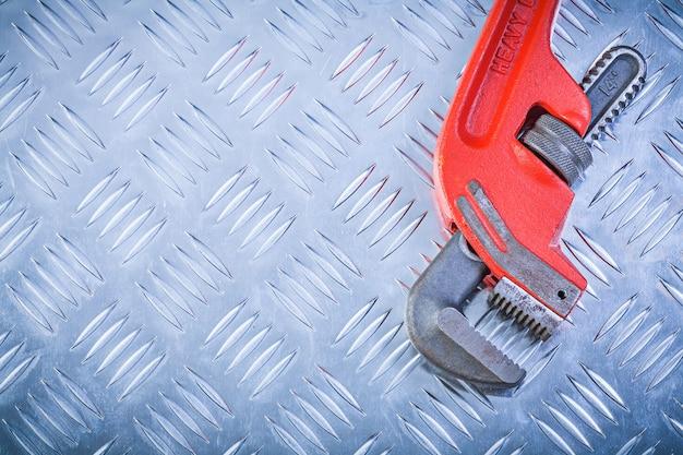 Metallroter schraubenschlüssel auf gerilltem metallischem hintergrund kopieren raumkonstruktionskonzept