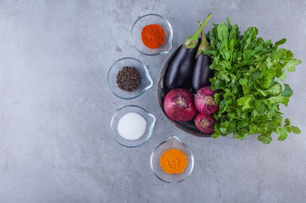 Metallschale mit auberginen, roten zwiebeln und petersilie mit verschiedenen gewürzen.