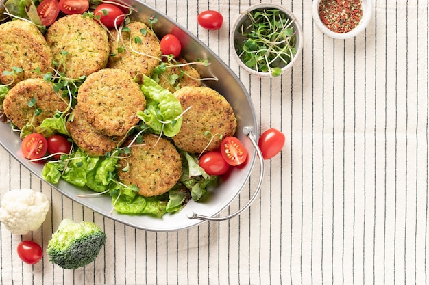 Metallschale mit veganen gemüseburgern und salat auf gestreifter tischdecke