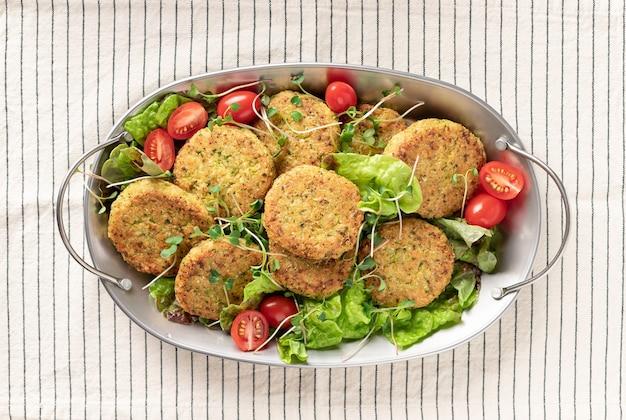 Metallschale mit veganen gemüseburgern und salat