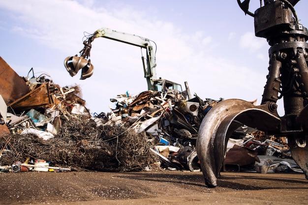 Metallschrottplatz mit hydraulischer hebemaschine mit klauenaufsatz für das altmetallrecycling.
