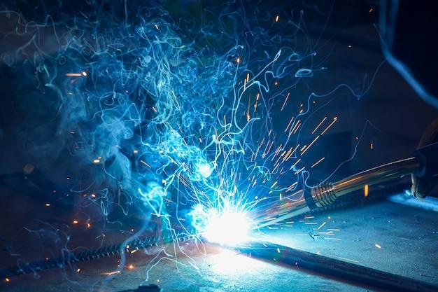 Metallschweißen. halbautomatisches schweißen von stangen und metallkonstruktionen in einer werkstatt einer ölraffinerie