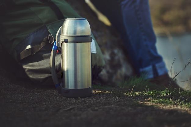 Metallstahl-thermoskanne des abenteurers. wandern, aktiver tourismus, picknick, heißgetränkekonzept.