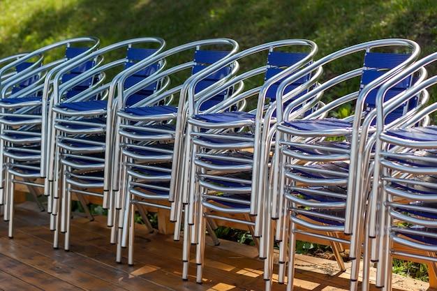 Metallstühle in haufen gestapelt und neben einem sonnenschirm in einem straßenrestaurant, café oder erholungszentrum. die stühle stehen auf dem holzboden. resorts warten auf touristen und besucher