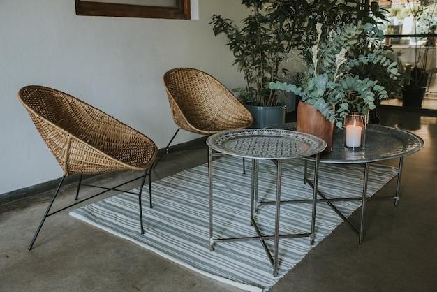 Metalltisch mit korbstühlen, holzvasen, teppich und spiegel
