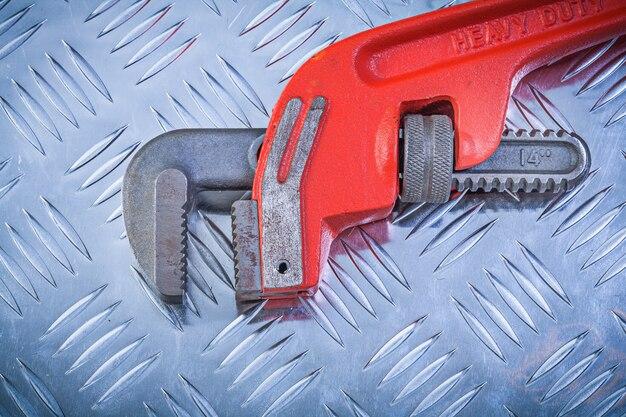 Metallverstellbarer schraubenschlüssel auf gerilltem metallischem hintergrundkonstruktionskonzept
