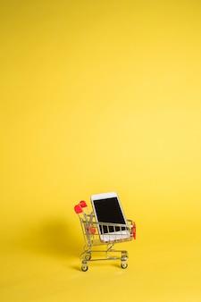 Metallwagen mit einem telefon auf einem gelben isolierten hintergrund mit platz für text. vertikale ausrichtung