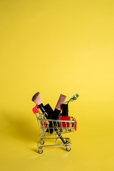 Metallwagen mit kosmetik auf einem gelben isolierten hintergrund mit platz für text. vertikale ausrichtung