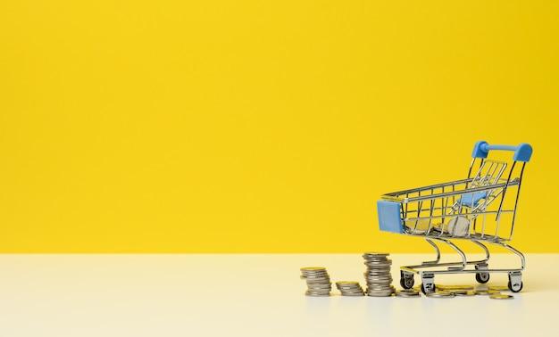 Metallwagen und kleingeld auf einem weißen tisch. sparkonzept, rabatte, geringe kaufkraft