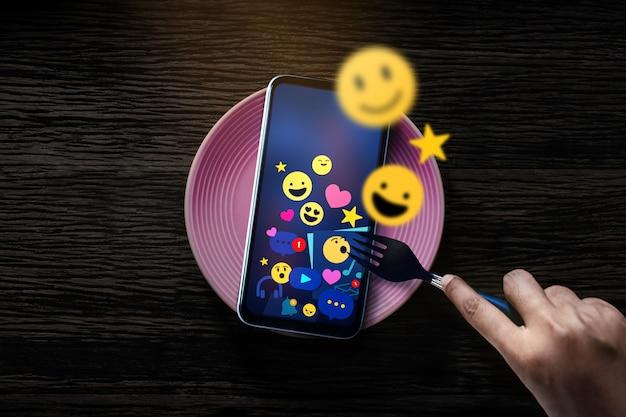 Metapher konzeptionelles foto. person, die gabel zum frühstücken mit social media emoji-symbolen auf dem handy verwendet. online-routine. lifestyle und technologie in der digitalen welt. tischansicht