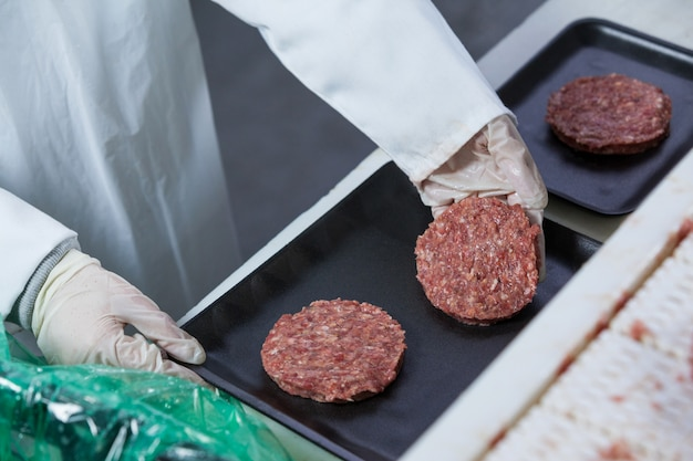 Metzger arrangiert hamburgerpastetchen auf tablett