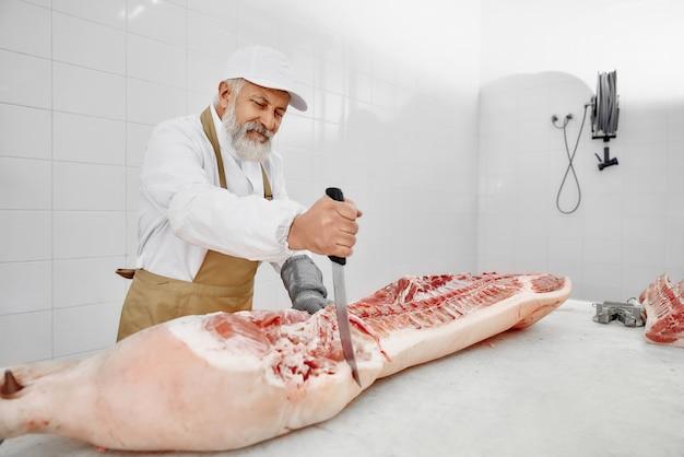 Metzger, der schweineschlachtkörper mit großem messer schneidet.