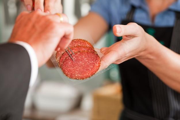Metzger showing fresh meat steaks zum kunden