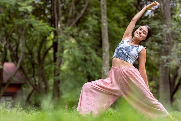 Mexikanerin beim yoga mit verschiedenen körperhaltungen im outdoor-park mit gras und bäumen im hinter...