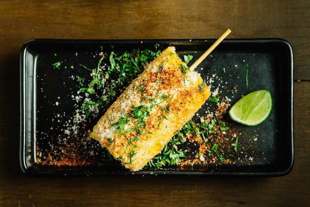 Mexikanische art gegrillte mais topping mit käse und chilipulver serviert mit geschnittenen limetten