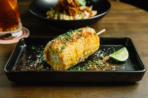 Mexikanische art gegrillte maissalat mit käse und chilipulver.